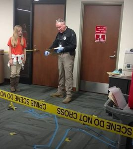 Detective explains how to investigate a crime scene at a recent Teen Science Café.