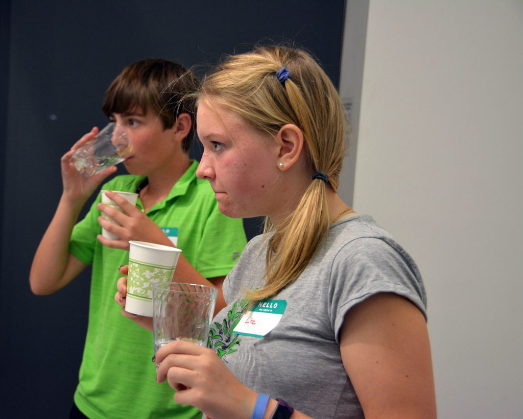 Kids tasting bottled water at Teen Science Café.