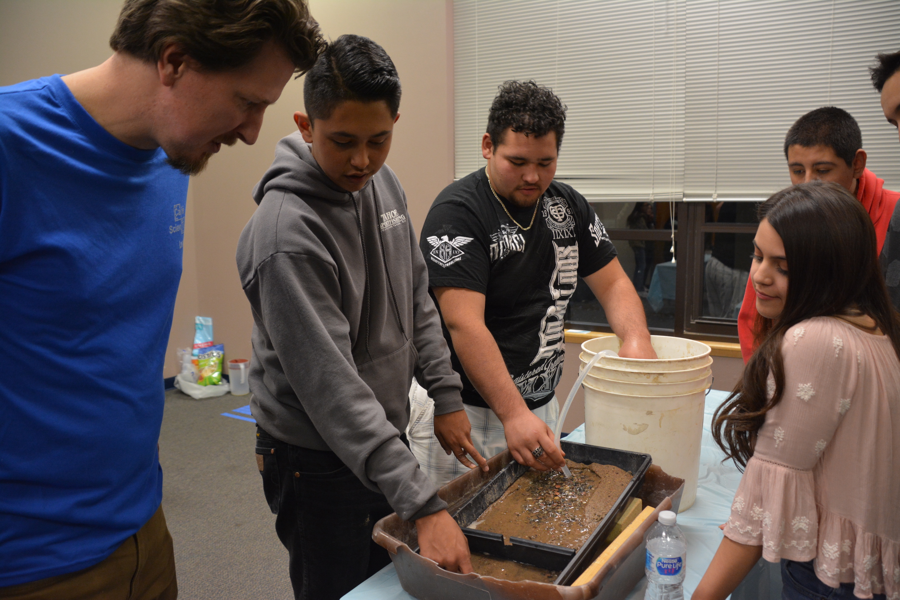 Teens learning about rivers with a flume.
