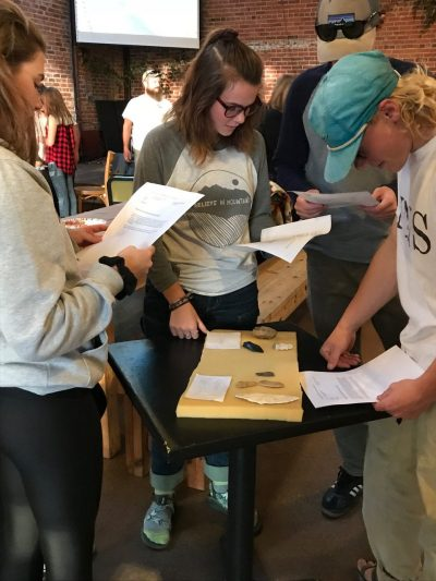 Students examine tools used by Neanderthals.